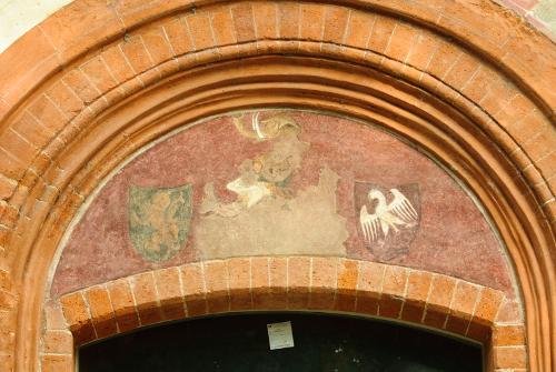 Sul lato piazza, con un Leone di Boemia, un elefante con le zanne e una aquila a volo abbassato. Probabilmente si riferisce a Paola Gonzaga, moglie di Gian Nicolò Trivulzio, figlio di Gian Giacomo Trivulzio, detto il Magno. I due si sposarono nel 1501.